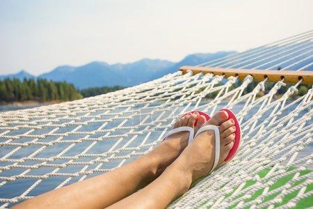 Photo pour Pieds et les jambes de la femme comme elle se détend dans un hamac en plein air tout en vacances et au repos sur un lac de montagne en arrière-plan - image libre de droit