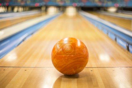 Photo pour Vue rapprochée d'une boule de bowling orange assise dans une allée de bowling colorée - image libre de droit