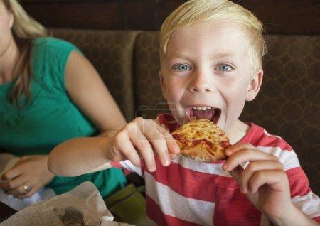 boy taking biteof pizza