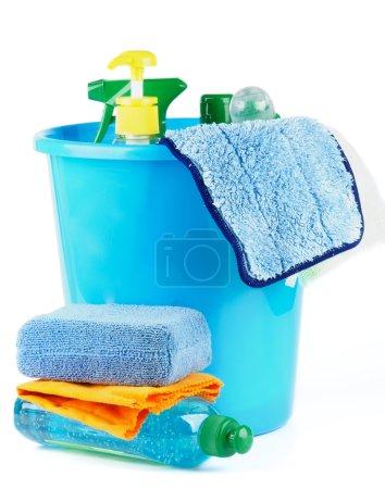 Photo pour Arrangement de nettoyage des bouteilles et des pulvérisations dans un seau bleu avec éponge de bain isolé sur fond blanc - image libre de droit