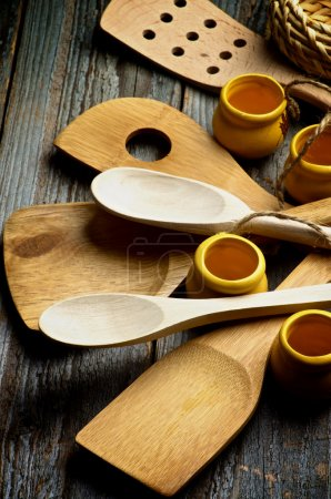 Photo pour Arrangement des ustensiles de cuisine avec des cuillères en bois, la spatule et le plan rapproché de petits pots sur le fond en bois rustique - image libre de droit