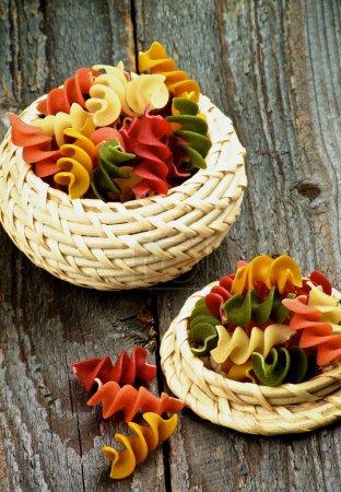 Photo pour Pâtes multicolores de Rotini dans le plan rapproché de cuiseau de cuvettesur le fond en bois rustique - image libre de droit