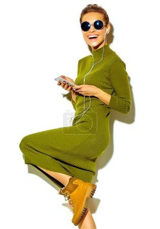 Photo pour Portrait de belle heureuse souriante femme brune fille mignonne en vêtements d'été décontracté vert hipster sans maquillage isolé sur blanc dans l'écoute de musique en smartphone avec un casque de lunettes de soleil - image libre de droit