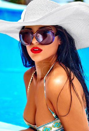 fashion photo of sexy hot beautiful girl model with dark hair in blue colorful swimwear posing in swimming pool with red lips in white big hat