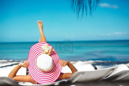 Beautiful woman model sunbathing on the beach chair in white bikini in colorful sunhat behind blue summer water ocean