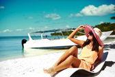 Krásná žena model opalování na pláži židli v bílých bikinách v barevné klobouku proti slunci seběhla za modré letní vody oceánu