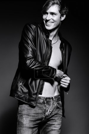 Young handsome muscled fit male model man in leather jacket posing in studio showing his abdominal muscles