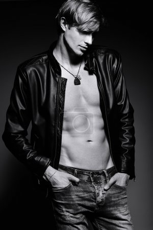 Photo for Young handsome muscled fit male model man in leather jacket posing in studio showing his abdominal muscles - Royalty Free Image
