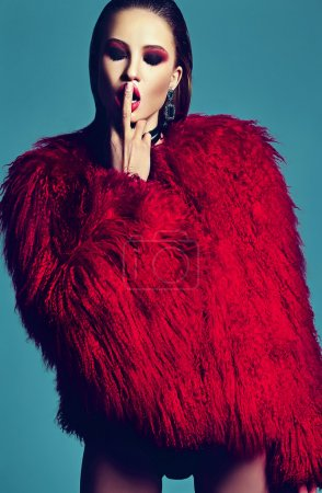 Fashion glamor stylish swag young woman model in hipster red fur coat with bright makeup on blue background