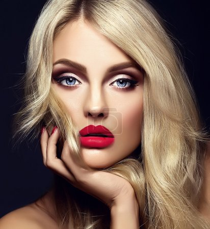 Photo for Sensual glamour portrait of beautiful blond woman model lady with bright makeup and red lips touching her face , with healthy curly hair on black background - Royalty Free Image