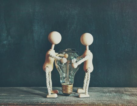 Wooden little men holding light bulb. Concept of e...