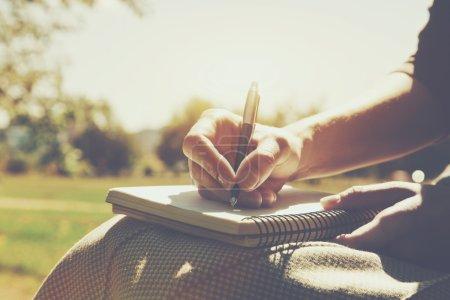 dłonie dziewczyny z piórem, pisanie na notebook w parku