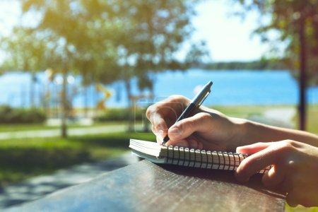 Photo pour Filles mains avec stylo écriture sur ordinateur portable dans le parc - image libre de droit