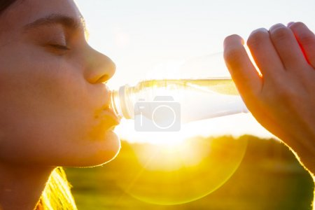 Woman drinking water in summer sunrise