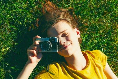 Photo pour Fille souriante couché dans l'herbe avec caméra de film - image libre de droit
