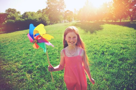 Happy redhead girl with pinwheel toy in park. Freedom, summer, c
