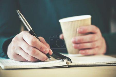 Photo pour Mains avec stylo écriture sur ordinateur portable avec café du matin - image libre de droit