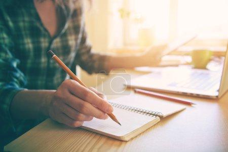 Photo pour La main avec un crayon et portable au milieu de travail - image libre de droit