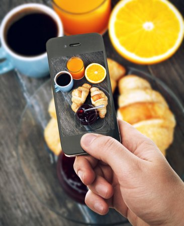 Photo for Hand with smartphone taking food photo of fresh breakfast with coffee and croissants - Royalty Free Image