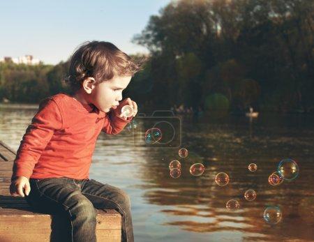 Photo pour Petit garçon soufflant des bulles de savon sur un lac - image libre de droit