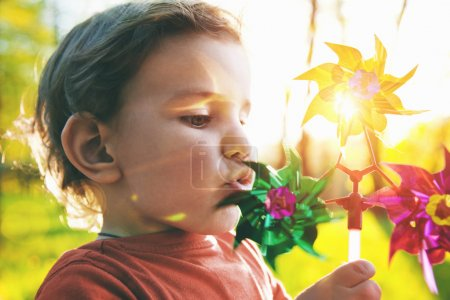 Photo pour Portrait d'un garçon mignon, soufflant la roue éolienne au soleil - image libre de droit