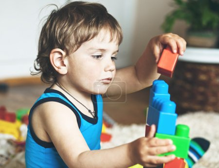 Photo for Cute boy playing with toy blocks and bricks - Royalty Free Image