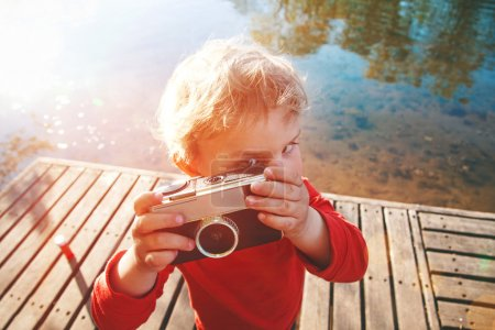 Photo for Portrait of a smiling cute boy taking picture with retro camera at a lake - Royalty Free Image