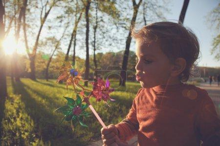 Photo pour Portrait d'un garçon mignon soufflant la roue du vent au soleil - image libre de droit