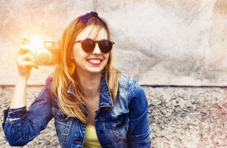 Photo for Smiling girl with vintage camera taking photo with flash on wall background. Copy space - Royalty Free Image