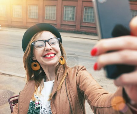 Photo for City lifestyle stylish hipster girl using a smartphone taking photo selfie with camera in a street - Royalty Free Image