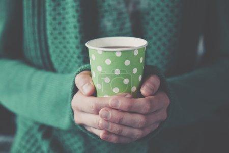 Hände halten Pappbecher mit Kaffee zum Mitnehmen