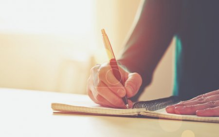 Photo for Female hands with pen writing on notebook - Royalty Free Image