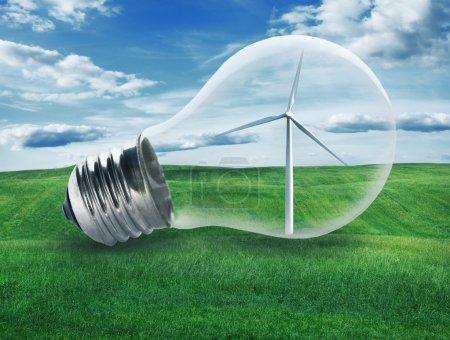 Light bulb with a wind turbine inside in green field. Environmen