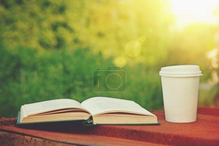 Taza de papel de café y libro en la hierba verde