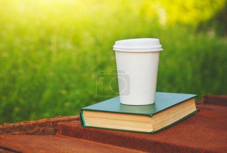 Photo pour Tasse de café en papier et réservez dans le parc du soleil d'été - image libre de droit