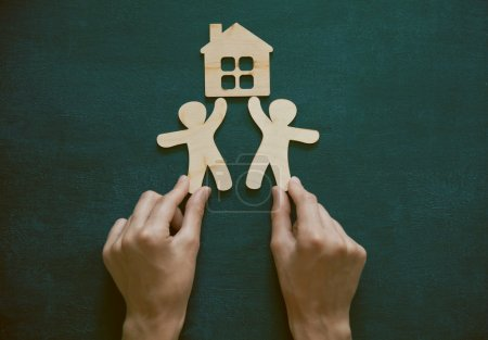 Hands holding wooden men and house on blackboard background