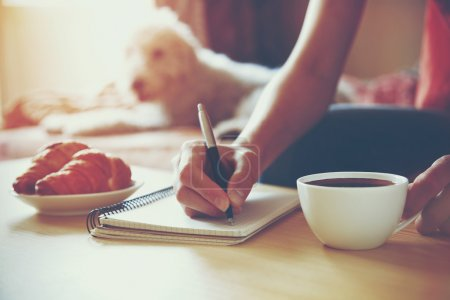 Photo for Female hands with pen writing on notebook with morning coffee and croissant - Royalty Free Image