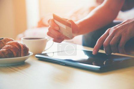 Photo pour Mains tenant la carte de crédit et en utilisant la tablette numérique PC avec café du matin et croissant. Achats en ligne . - image libre de droit