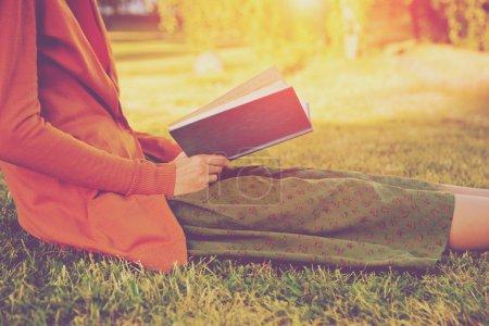 Photo pour Fille lecture livre au parc en été lumière - image libre de droit