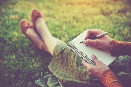 Photo pour Mains féminines avec stylo écriture sur ordinateur portable sur l'herbe à l'extérieur - image libre de droit