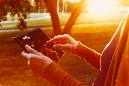 hands holding digital tablet pc in summer sunset light
