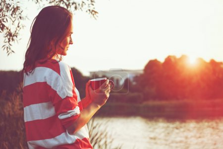 Photo for Pretty girl with morning coffee at river sunrise - Royalty Free Image