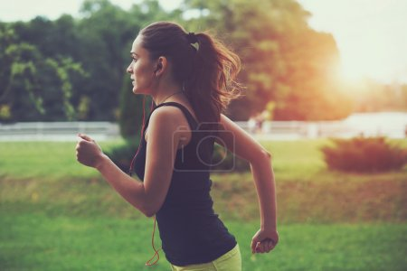 Photo for Pretty sporty woman jogging at park in sunrise light - Royalty Free Image