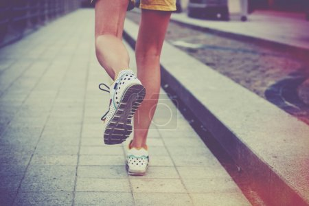 Girl jogging in park. Feet running on road