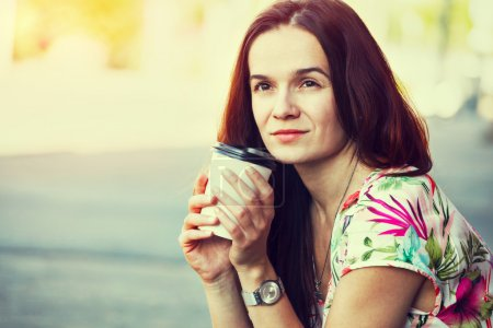 Photo for Pretty girl sitting in street with morning coffee - Royalty Free Image