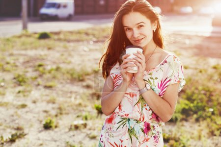 smiling pretty girl walking in street with morning coffee