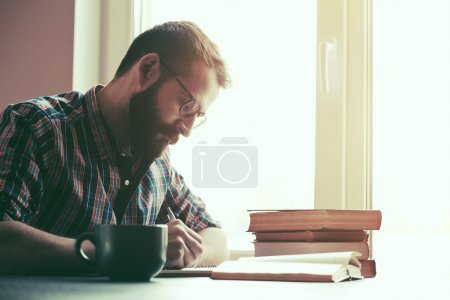 Bearded man writing with pen