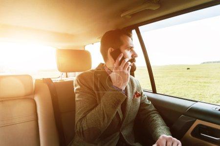 Photo pour Jeune homme d'affaires barbu beau assis sur le siège arrière de la voiture et parlant au téléphone - image libre de droit