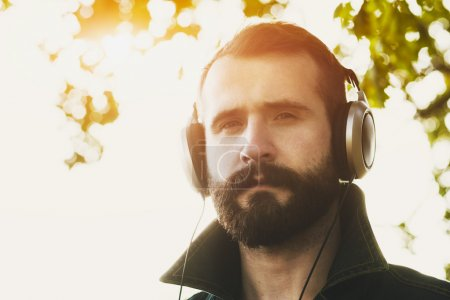Photo for Young stylish bearded man  in headphones listening to music - Royalty Free Image