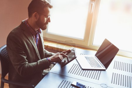 Photo for Young bearded man working with laptop and digital tablet in morning sunlight - Royalty Free Image